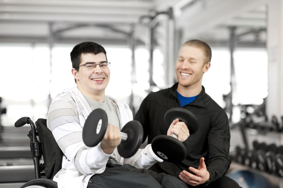 Disabled male in wheelchair working out with trainer.